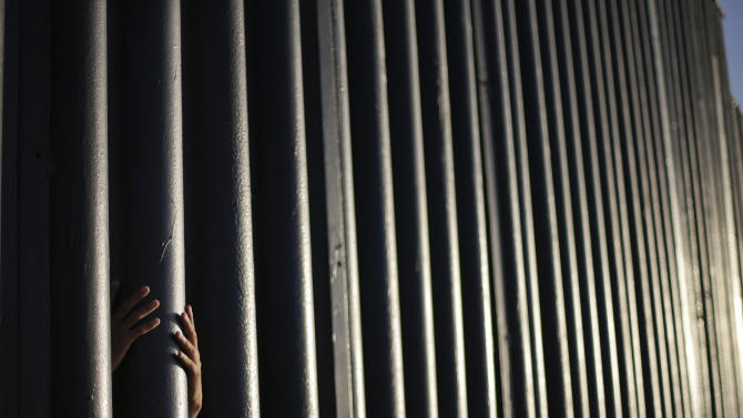 AP10ThingsToSee - Daniel Zambrano, of Tijuana, Mexico, holds one of the bars that make up the border wall separating the U.S. and Mexico where the border meets the Pacific Ocean, Thursday, June 13, 2013 in San Diego. Illegal immigration into the United States would decrease by only 25 percent under a far-reaching Senate immigration bill, according to an analysis by the Congressional Budget Office that also finds the measure reduces federal deficits by billions. (AP Photo/Gregory Bull, File)