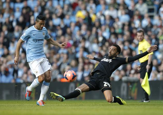 Wigan Athletic's Perch challenges Manchester City's Clichy during their English FA Cup quarter final soccer match at the Etihad stadium in Manchester