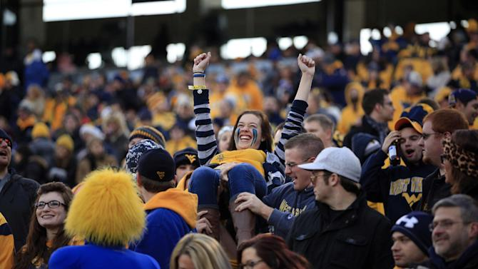 A West Virginia fan is lifted by the crowd as they celebrate a touchdown during the first quarter of their NCAA college football game against Iowa State in Morgantown, W.Va., on Saturday, Nov. 30, 2013. Iowa State won 52-44 in triple-overtime