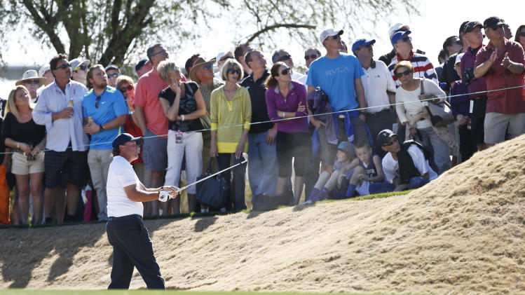 As the gallery looks on, Phil Mickelson hits out of a fairway bunker on the third hole during the second round of the Waste Management Phoenix Open golf tournament on Friday, Feb. 1, 2013, in Scottsdale, Ariz. (AP Photo/Ross D. Franklin)