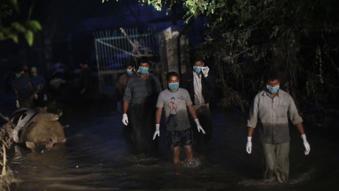 Government workers wade through flood waters after pulling out the carcasses of cows from an inundated Indian army dairy farm in Srinagar, Indian-controlled Kashmir, Tuesday, Sept. 16, 2014. Health workers were scrambling Tuesday to manage a mounting health crisis nearly two weeks after massive flooding engulfed much of Kashmir, where they are treating cases of diarrhea, skin allergies and fungus as they hope the stagnant waters do not create conditions for more serious disease outbreaks. (AP Photo/Altaf Qadri)