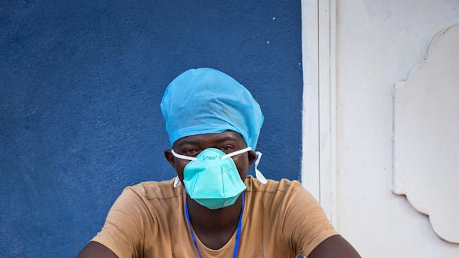 In this Sept. 19, 2014 photo, an Ebola virus health care worker takes a rest outside a Ebola isolation unit in Freetown, Sierra Leone.   Sierra Leone confined its 6 million people to their homes Friday for the next three days as the Ebola-ravaged West African country began what was believed to be the most sweeping lockdown against disease since the Middle Ages. (AP Photo/Michael Duff)