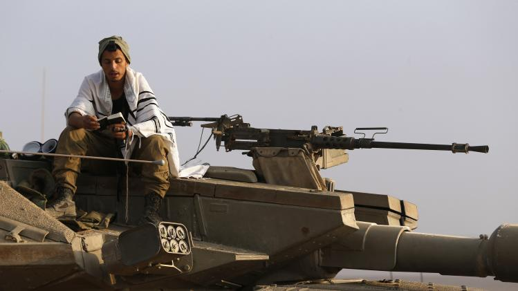 An Israeli soldier prays atop a tank near the border with Gaza