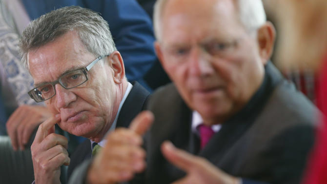 German Interior Minister De Maiziere and Finance Minister Schaueuble await start of cabinet meeting in Berlin