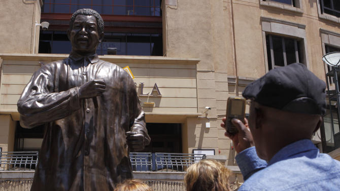 "People take photos of the giant statue of former president Nelson Mandela, in Mandela Square, Johannesburg, South Africa, Sunday Dec. 9, 2012. South Africans prayed Sunday for the health of former President Nelson Mandela and anxiously awaited further word about the anti-apartheid leader after he was admitted to a military hospital. President Jacob Zuma visited Mandela Sunday morning at the hospital in Pretoria and found the frail 94-year-old to be ""comfortable and in good care,"" presidential spokesman Mac Maharaj said in a statement. Maharaj offered no other details about Mandela, nor what medical tests he had undergone since entering the hospital Saturday.  (AP Photo/Denis Farrell)"