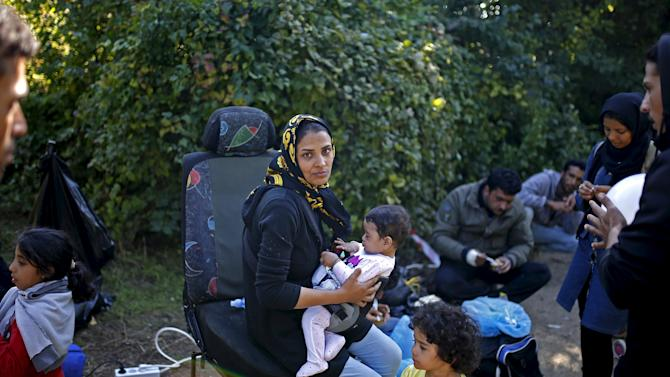 Migrants rest during their journey to cross the border from Serbia to Croatia, near the village of Berkasovo,
