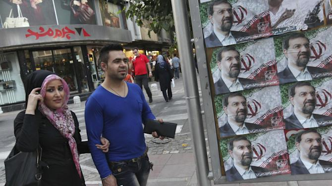 Iranians walk past posters of the presidential candidate Mohsen Rezaei, a former Revolutionary Guard commander, a day prior to the election, in Tehran, Iran, Thursday, June 13, 2013. (AP Photo/Vahid Salemi)