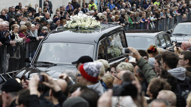 FILE - Crowds of people throng the route to watch the funeral cortege for Sir Jimmy Savile pass by in this file photo dated Wednesday Nov. 9, 2011, in Leeds, England.  A year ago Savile was a cultural icon, but now on the first anniversary of the funeral, his reputation is laid low, his grave stone removed, and the people who revered him are trying to come to terms with his alleged sex crimes. (AP Photo/Jon Super, File)