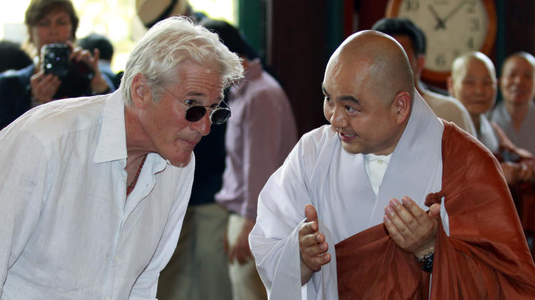 U.S. actor Richard Gere, left, listens to monk Sung Jin during his visit to the Korean Buddhism's Chogye temple in Seoul, South Korea, Tuesday, June 21, 2011. Gere is in South Korea for six days to promote his photo exhibition and tour Buddhist temples. (AP Photo/ Lee Jin-man, Pool)