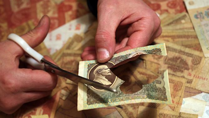 In this photo taken Friday, Feb. 8, 2013, Belarus artist Igor Arinich cuts  a Soviet era banknote while making a piece of art in Minsk, Belarus. Arinich has used Soviet banknotes which he buys at local flea markets in Belarus for his works. (AP Photo/Sergei Grits)