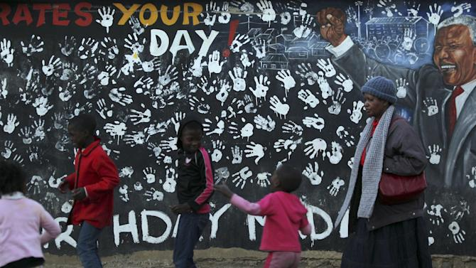 A young girl plays in front a mural depicting former South African President Nelson Mandela at the Alexandra township in Johannesburg, South Africa, Tuesday, July 17, 2012, to honor Mandela's 94th birthday which is celebrated Wednesday, July 18, 2012. (AP Photo/Themba Hadebe)