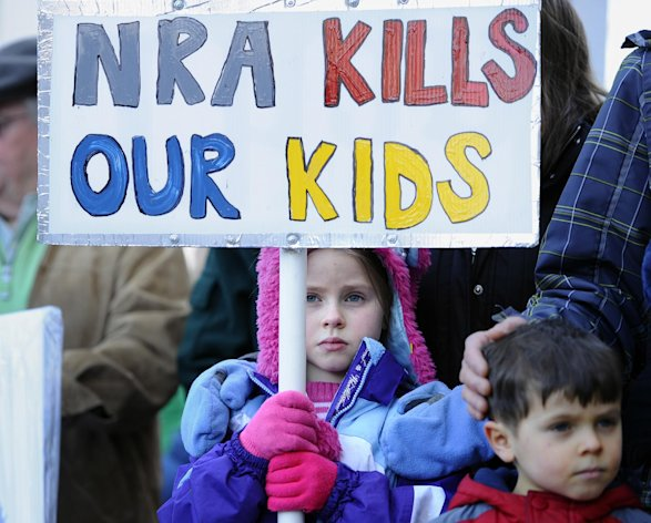 Abigail Garrett of Hampden holds a saign during a rally at the Capitol in Hartford, Conn., Thursday, Feb. 14, 2013. Thousands of people turned out to call on lawmakers to toughen gun laws in light of the December elementary school shooting in Newtown that left 26 students and educators dead. (AP Photo/Jessica Hill)