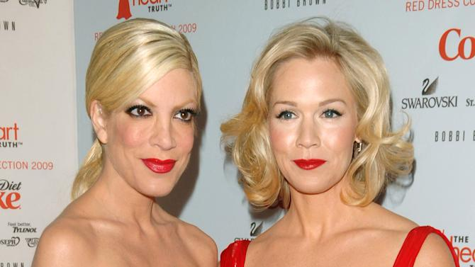 """FILE - This Feb. 13, 2009 file photo shows actors Tori Spelling, left, and Jennie Garth at the Heart Truth's Red Dress collection during Fashion Week in New York. Former """"Beverly Hills, 90210"""" stars Jennie Garth and Tori Spelling are reuniting. The actresses will co-star and executive produce the new ABC Family series """"Mystery Girls."""" In the series, Spelling and Garth play Holly and Charlie, who were on a crime-solving series in the 90's that was the highest-rated show on TV. Spelling's Holly is looking to reignite her fame and opens a detective agency. She persuades Charlie, now a suburban mom to help. """"Mystery Girls"""" is set to shoot in November. (AP Photo/Peter Kramer, File)"""