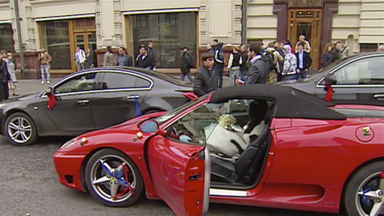 In this video grab taken on Sunday, Sept. 30, 2012, and provided by Russian Television channel shows wedding guests and passers-by standing around a red sports Ferrari that was pulled over by police after celebratory firing in the air in Moscow. The shooting that was part of a Caucasus wedding ritual prompted a public outcry in Russia amid growing xenophobia and ethnic tensions between Slavs and predominantly Muslim natives of the volatile Caucasus region. (AP Photo/Russian Television via AP Television)