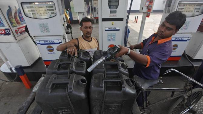 A worker prepares to fill a jerry-can at a fuel station in Kolkata