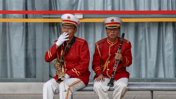 Members of a music band smoke cigarettes on a bench as they take a break, in Kunming