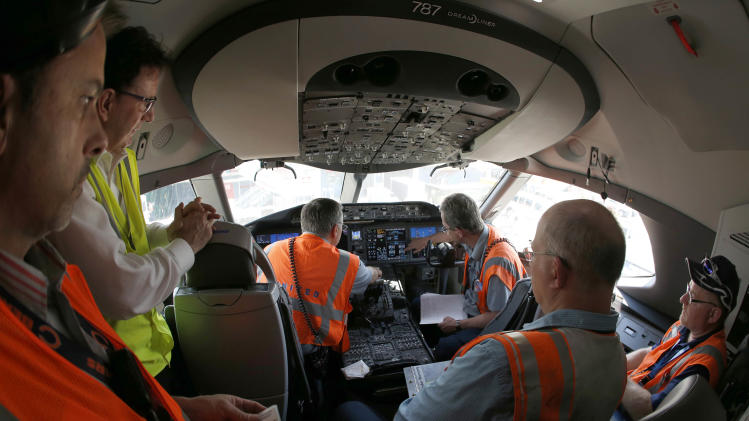 United Airlines employees learn about performing ground checks on flight a Boeing 787 Dreamliner aircraft from Houston, Texas, after it landed at Chicago's O'Hare International Airport Monday, May 20, 2013.  The planes are returning after being grounded for four months by the federal government because of smoldering batteries on 787s owned by other airlines. (AP Photo/Charles Rex Arbogast)