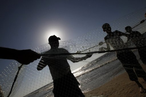 Palestinian fishermen clean their nets off the coast of Nusseirat refugee camp, in the central Gaza Strip, on September 19, 2012. An economic crisis gripping the Palestinian territories has exacerbated growing frustration over deadlock in the peace process