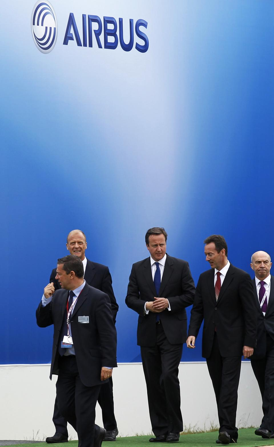 Britain's Prime Minister David Cameron, center, walks with President of Airbus Fabrice Bregier, second right, as he arrives to visit the Airbus display during the Farnborough International Airshow, Farnborough, England, Monday, July 9, 2012. (AP Photo/Sang Tan)
