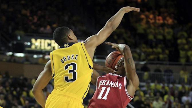 Michigan guard Trey Burke (3) jumps to attempt a block on Arkansas guard BJ Young (11) during the first half of an NCAA college basketball game in Ann Arbor, Mich., Saturday, Dec. 8, 2012. (AP Photo/Carlos Osorio)