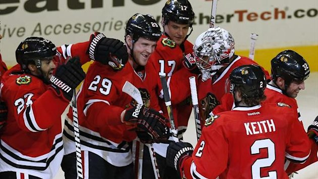 Chicago Blackhawks' goalie Ray Emery (3rd R) is surrounded by team-mates after his team's win over the Vancouver Canucks (Reuters)