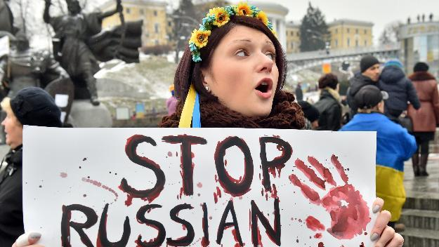 """A woman holds a placard reading """"Stop Russian aggression"""" during a rally on Independence Square in Kiev, on January 25, 2015"""