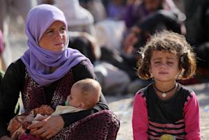 A Iraqi Yazidi woman sits with her children at the…