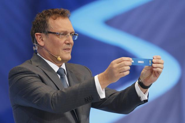 "Valcke holds up the slip showing ""Greece"" during the draw for the 2014 World Cup in Sao Joao da Mata"