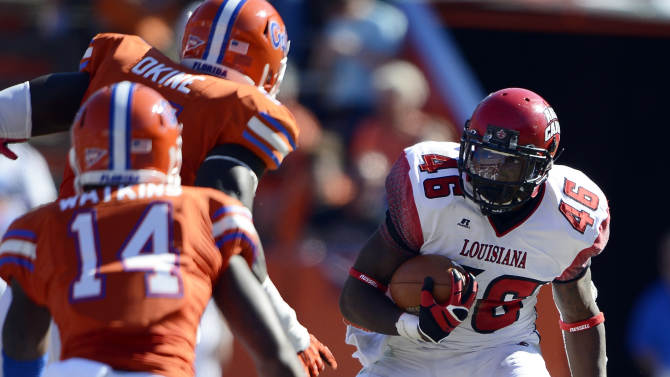 Louisiana-Lafayette running back Alonzo Harris (46) tries for yardage but is confronted with Florida's Earl Okine (91) and Jaylen Watkins (14)  during the first half of an NCAA college football game in Gainesville, Fla., Nov. 10, 2012.  (AP Photo/Phil Sandlin)