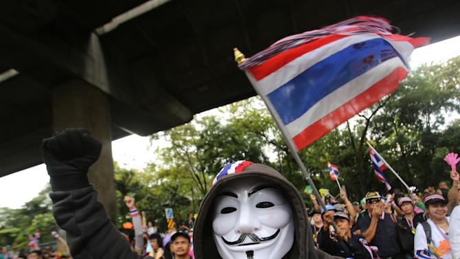 """An anti-government protester wearing an Anonymous mask joins others outside the Industry Ministry in Bangkok, Thailand, Wednesday, Nov. 27, 2013. Protesters vowing to topple Thai Prime Minister Yingluck Shinawatra took to the streets for a fourth straight day on Wednesday, declaring they would take over """"every ministry"""" of the government. The brash threat is the biggest challenge yet to the embattled premier's administration, raising fears of fresh political violence in the Southeast Asian nation. (AP Photo/Sakchai Lalit)"""