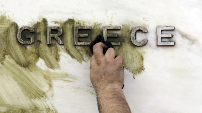 A worker cleans graffiti off the Bank of Greece logo, outside the central bank's headquarters in Athens, Monday, Nov. 26, 2012. The ministers of the 17 countries that use the euro are meeting in Brussels later Monday to try to reach an agreement on disbursement of Greece's next rescue loan installment, after several delays. Athens faces bankruptcy without the cash. (AP Photo/Thanassis Stavrakis)