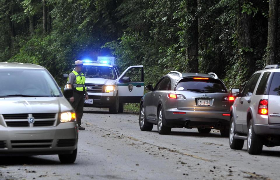 A National Park Service ranger turns traffic away from an entrance to the Great Smoky Mountains National Park Friday, July 6, 2012, in Townsend, Tenn. At least two park visitors were killed and others injured by a violent storm that swept through the Cades Cove area Thursday evening. (AP Photo/The Knoxville News Sentinel, J. Miles Cary)
