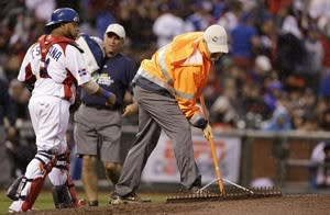 The Dominican Republic's Carlos Santana, left watches as a member of the grounds crew rakes the mound under rain during the fifth inning of the championship game of the World Baseball Classic against Puerto Rico in San Francisco, Tuesday, March 19, 2013. (AP Photo/Eric Risberg)