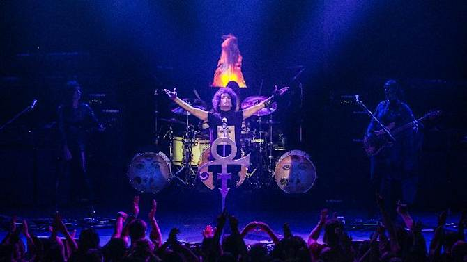"""In this 2014 photo released by NPG Records, Prince performs at The Roundhouse in London. On Tuesday, Sept. 30, 2014, Prince will release his first album in four years, """"Art Official Age,"""" along with music from his latest protege act, 3RDEYEGIRL, """"PLECTRUMELECTRUM."""" (AP Photo/NPG Records)"""