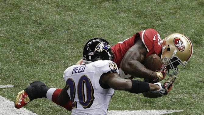 San Francisco 49ers tight end Vernon Davis (85) is tackled by Baltimore Ravens safety Ed Reed (20) during the first half of NFL Super Bowl XLVII football game, Sunday, Feb. 3, 2013, in New Orleans. (AP Photo/Charlie Riedel)