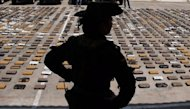 "A Colombian policewoman from an anti-drug unit stands by packages of cocaine, part of a seizure of 1,825 kg worth $3 million, in Rioacha, Guajira deparment, Colombia on September 16, 2012. The drugs belonged to the ""Los Urabenos"" drug traffickers gang"