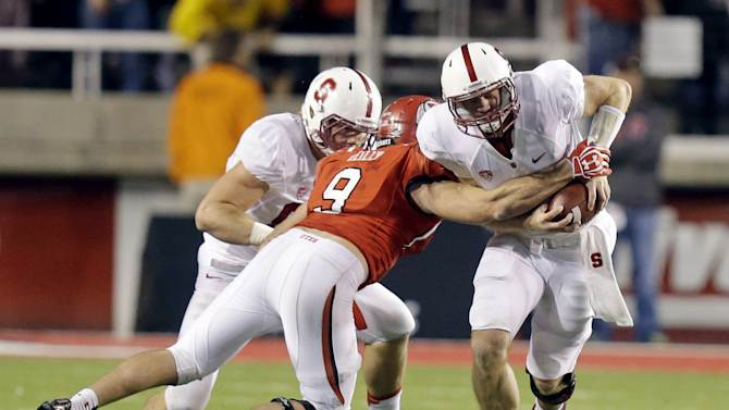 Utah's Trevor Reilly (9) tackles Stanford quarterback Kevin Hogan, right, during the fourth quarter of an NCAA college football game on Saturday, Oct. 12, 2013, in Salt Lake City. (AP Photo/Rick Bowmer)