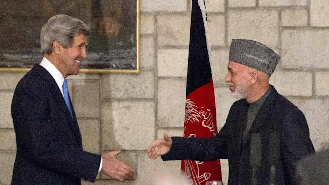 """Secretary of State John Kerry reaches to shakes hands with Afghan President Hamid Karzai at the end of their joint news conference at the Presidential Palace in Kabul, Monday, March 25, 2013. Kerry and Karzai made a show of unity Monday, shortly after the U.S. military ceded control of its last detention facility in Afghanistan, ending a longstanding irritant in relations between the two countries. Kerry, in Afghanistan for an unannounced visit, said he and Karzai were """"on the same page"""" when it comes to peace talks with the Taliban. (AP Photo/Jason Reed, Pool)"""