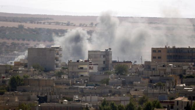 Smoke rises over the Syrian town of Kobani near the Mursitpinar border crossing, on the Turkish-Syrian border, as seen from the southeastern town of Suruc