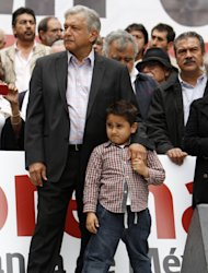 Former presidential candidate Andres Manuel Lopez Obrador stands with his son, Jesus Ernesto, during an act to protest against the governments proposed energy reforms that would allow private companies to explore the country's oil and gas reserves, in Mexico City, Sunday Sept. 8, 2013. The proposed reform requires constitutional changes that strike at the heart of one of Mexico's proudest moments: President Lazaro Cardenas' nationalization of the oil company in 1938. (AP Photo/Marco Ugarte)