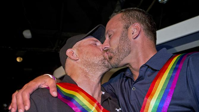 In this photo provided by the Florida Keys News Bureau, William Lee Jones, left, and Aaron Huntsman kiss during a celebration Thursday, July 17, 2014, in Key West, Fla. Jones and Hunstman and about 100 other people marked a Florida Keys judge's ruling overturning Florida's ban on same-sex marriage on Thursday after the couple's legal challenge. (AP Photo/Florida Keys News Bureau, Andy Newman)
