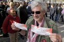 A Rolling Stones fan displays two tickets he purchased for a short warm-up gig in Paris