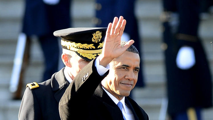 President Barack Obama, followed by US Army Maj. Gen. Michael J. Linnington waves  on Capitol Hill in Washington, Monday, Jan. 21, 2013, after the Presidential review of the troops on the east side of the Capitol following his Inaugural address and ceremonial swearing-in ceremony during the 57th Presidential Inauguration. (AP Photo/CJ Gunther, Pool)