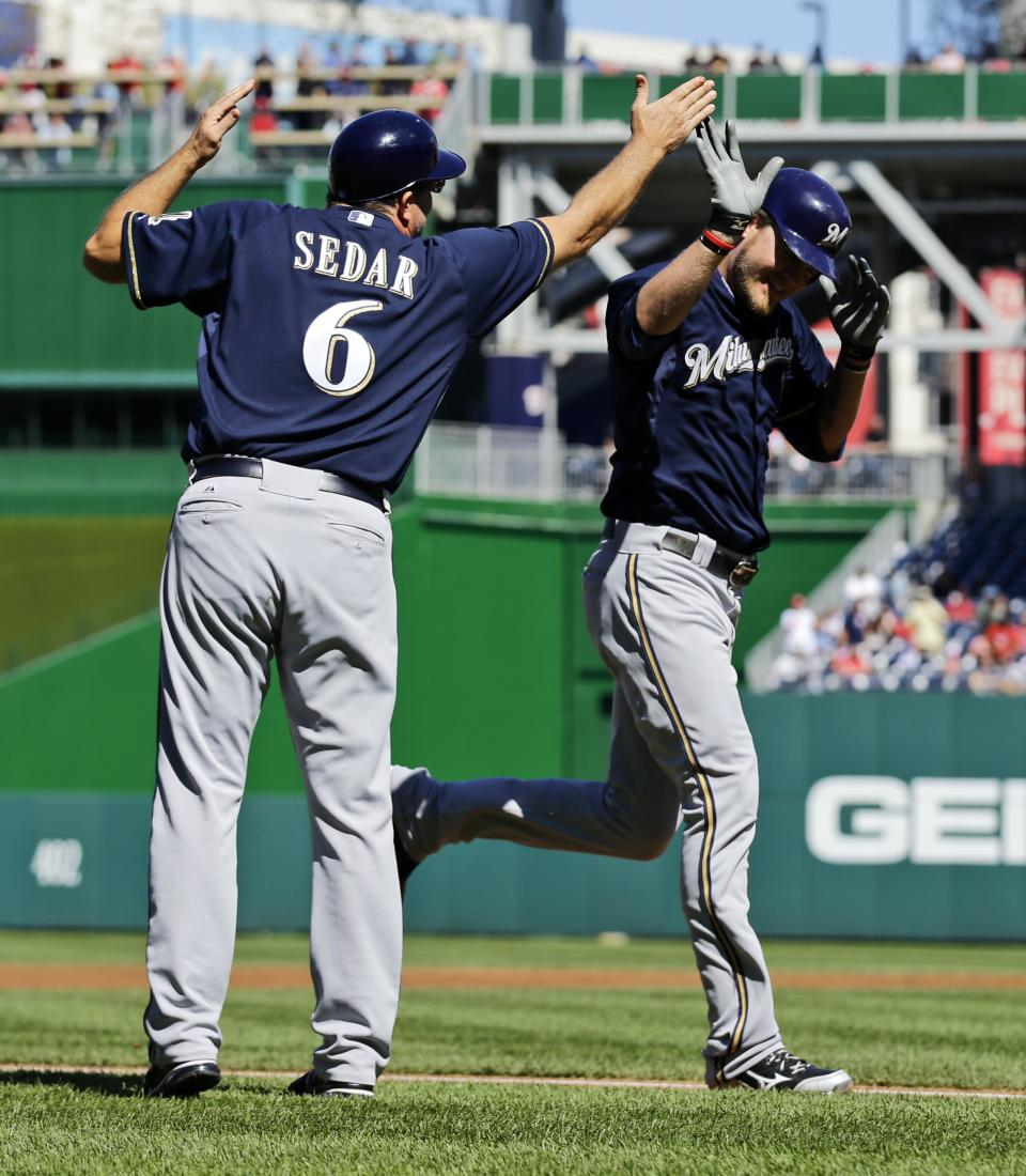 Milwaukee Brewers' Corey Hart, right, celebrates with third base coach Ed Sedar during his solo home run in the second inning of a baseball game against the Washington Nationals at Nationals Park, Monday, Sept. 24, 2012, in Washington. (AP Photo/Alex Brandon)