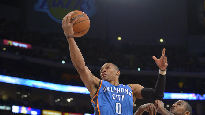 Oklahoma City Thunder guard Russell Westbrook, center, goes up for a shot as Los Angeles Lakers guard Chris Duhon, left, and forward Earl Clark defend during the second half of their NBA basketball game, Friday, Jan. 11, 2013, in Los Angeles. The Thunder won 116-101. (AP Photo/Mark J. Terrill)