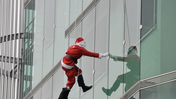 A member of the special police force dressed in a Santa suit, descends from the roof of a paediatric clinic in Ljubljana, as part of a Christmas performance for patients of the clinic