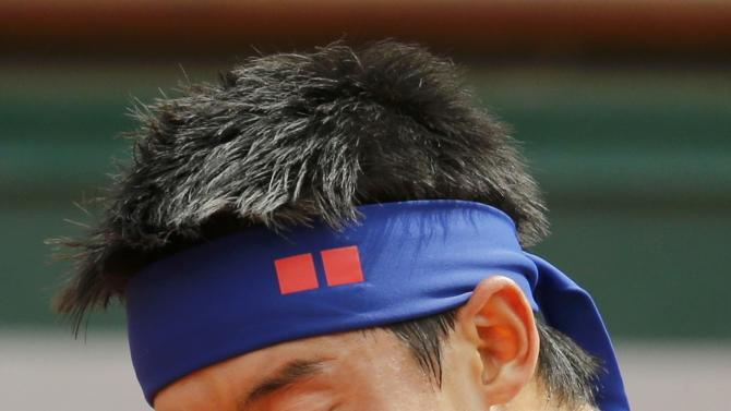 Kei Nishikori of Japan wipes his face during his men's quarter-final match against Jo-Wilfried Tsonga of France during the French Open tennis tournament at the Roland Garros stadium in Paris