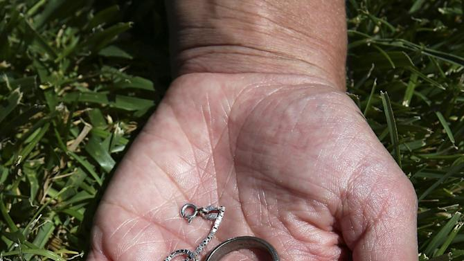 Danica Weeks holds her husband's wedding ring which he gave her prior to boarding Flight MH370,  during a visit to Australia's Parliament House in Canberra, Australia, Thursday, March 5, 2015. Weeks and her two sons are in Canberra to meet prime minister Tony Abbott and attend a briefing with officials about the ongoing search efforts for the plane that has been missing since March 8, 2014.(AP Photo/Rob Griffith)