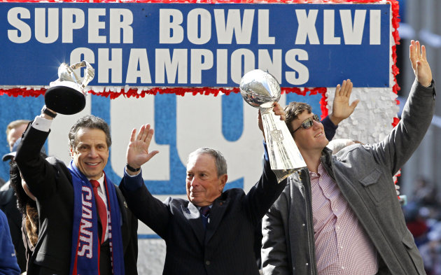 New York Gov. Andrew Cuomo, left, holds the Halas Trophy, while New York Mayor Michael Bloomberg, center, holds the Vince Lombardi Trophy as New York Giants quarterback Eli Manning, right, waves to th