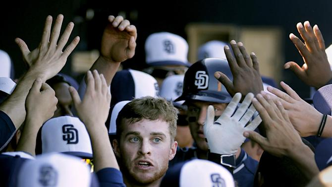 San Diego Padres' Cory Spangenberg celebrates in the dugout after scoring on a single by Alexi Amarista during the third inning of a spring training baseball game against the Seattle Mariners, Thursday, March 5, 2015, in Peoria, Ariz. (AP Photo/Charlie Riedel)